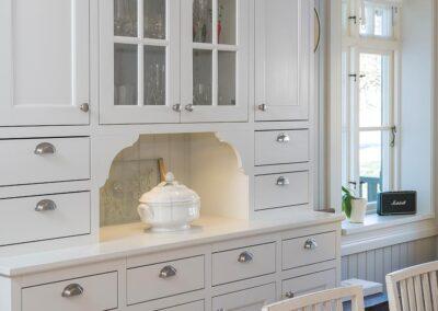 Platsbyggt kök i allmogestil med inpassade spegelluckor av massiv björk penselmålade med linoljefärg och tidstypiska klassiska skålhandtag - Wernerssons Snickeri