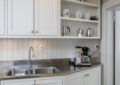 Platsbyggt kök i allmogestil med inpassade spegelluckor av massiv björk penselmålade med linoljefärg, rejäl diskbänk i rostfritt stål med uppdragen bakkant - Wernerssons Snickeri
