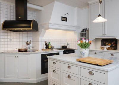 Platsbyggt kök i allmogestil med inpassade spegelluckor av massiv björk. Bänkskivor av Carrara marmor - Wernerssons Snickeri