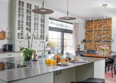 Platsbyggt kök i klassisk stil helt i massiv ask. Köksöns bänkskiva i 6 mm rostfritt stål ger en modern touch - från Wernerssons Snickeri