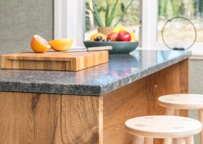 Modernt stilrent kök med mycket naturkänsla. Köksö med stomme av breda ekplank och mattslipad granitskiva - från Wernerssons Snickeri