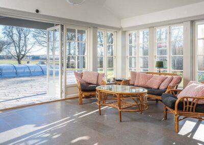 Ihop med ett platsbyggt lantkök tillverkade och monterade dörrar och fönster med spröjs till en inglasad veranda på huset. Allt byggt av Wernerssons Snickeri